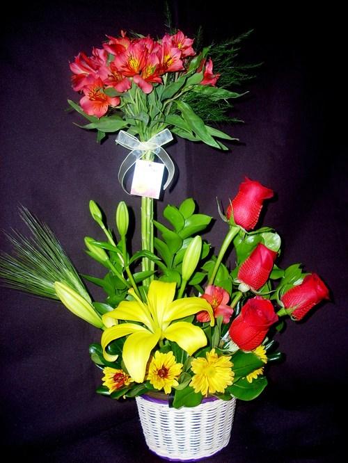 Delicado arreglo con rosas, astromelias, lilium en cesta de mimbre.