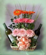 Gerberas and wine in wicker baskets